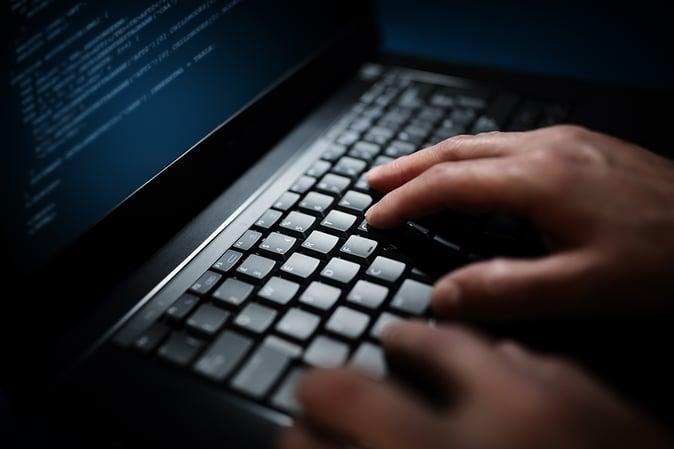 programmer-or-computer-hacker-typing-on-laptop-PSAN67J